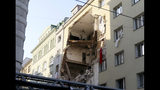 Firefighters search through the rubble of a exploded building in Vienna, Austria, Wednesday, June 26, 2019. A suspected gas explosion blew a gaping hole in a building in central Vienna on Wednesday, injuring at least 12 people, two of them seriously, according to police and images from the scene. (AP Photo/Ronald Zak)