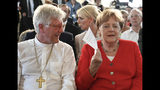 German Chancellor Angela Merkel fans herself with a piece of paper to cool down as she sits next to Heinrich Bedford-Strohm, Council President of the Evangelical Church in Germany, during the annual reception of the Evangelical Church in Germany in Berlin, Wednesday June 26, 2019. (Ralf Hirschberger/dpa via AP)
