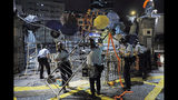 Riot police clear barricades blocked by protesters outside the police headquarters as thousands gathered to demand for an independent inquiry into a heavy-handed police crackdown at a protest earlier this month, in Hong Kong during the early hours of Thursday, June 27, 2019. Thousands of people joined Hong Kong's latest protest rally Wednesday night against legislation they fear would erode the city's freedoms, capping a daylong appeal to world leaders ahead of a G-20 summit this week that brings together the heads of China, the United States and other major nations. (AP Photo/Kin Cheung)