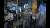 Riot police walk over barricades blocked by protesters outside the police headquarters as thousands gathered to demand for an independent inquiry into a heavy-handed police crackdown at a protest earlier this month, in Hong Kong during the early hours of Thursday, June 27, 2019. Thousands of people joined Hong Kong's latest protest rally Wednesday night against legislation they fear would erode the city's freedoms, capping a daylong appeal to world leaders ahead of a G-20 summit this week that brings together the heads of China, the United States and other major nations. (AP Photo/Kin Cheung)