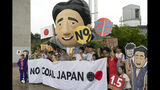 Environmental activists and local residents chant slogans as they stand next to an inflatable depicting Japanese Prime Minister Shinzo Abe during a protest in front of a coal-fired power plant ahead of the G-20 Summit Thursday, June 27, 2019, in Kobe, western Japan. The protesters demanded an end to coal funding. (AP Photo/Jae C. Hong)