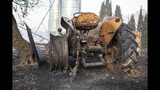 A burned farm tractor lays destroyed after a wildfire swept through Torre de l'Espanyol, near Tarragona, Spain, Thursday, June 27, 2019. The Catalonia region of Spain has seen its biggest forest fire this year, with more than 1,200 hectares (3,000 acres) believed to have been burned and hundreds of people evacuated. (AP Photo/Jordi Borras)