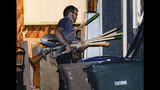 """Police investigators carry in multiple rakes and shovels into the backyard of a home at 547 N. 1000 West in Salt Lake City as part of the disappearance of University of Utah student MacKenzie Lueck on Wednesday, June 26, 2019. Police said Thursday that the owner of a home they searched in connection with the disappearance is a """"person of interest"""" and that they are trying to find a mattress that had been inside his home. (Francisco Kjolseth/The Salt Lake Tribune via AP)"""
