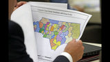 In this photo taken Wednesday, July 26, 2017 a lawmaker studies a district map during a joint select committee meeting on redistricting in Raleigh, N.C. North Carolina's nearly continuous legal battles this decade over how maps for state district boundaries are drawn don't end with a landmark U.S. Supreme Court decision refusing to try to recalibrate boundaries to repair aggrieved political imbalances. (AP Photo/Gerry Broome)