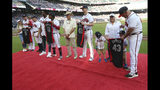 Atlanta Braves All-Stars Freddie Freeman, Ronald Acuna Jr., Mike Soroka and manager Brian Snitker, from left, are presented their All-Star jerseys by family and friends before the team's baseball game against the Philadelphia Phillies on Tuesday, July 2, 2019, in Atlanta. (Curtis Compton/Atlanta Journal-Constitution via AP)