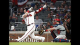 Atlanta Braves third baseman Josh Donaldson (20) follows through on a home run in front of Philadelphia Phillies catcher J.T. Realmuto (10) during the fourth inning of a baseball game Thursday, July 4, 2019, in Atlanta. (AP Photo/John Bazemore)