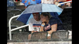 Fans take cover during a rain delay in the eighth inning of a baseball game between the Miami Marlins and the Atlanta Braveson Friday, July 5, 2019, in Atlanta. (AP Photo/John Bazemore)