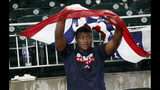 A fan takes cover under a piece of decorative bunting during a rain delay in the eighth inning of a baseball game between the Miami Marlins and the Atlanta Braves on Friday, July 5, 2019, in Atlanta. (AP Photo/John Bazemore)