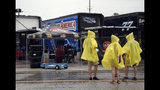 Race fans walk through the garage area during a weather delay before the NASCAR Cup Series auto race at Daytona International Speedway, Saturday, July 6, 2019, in Daytona Beach, Fla. (AP Photo/Phelan Ebenhack)