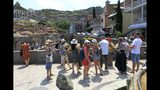 FILE - In this file photo taken on Saturday, June 22, 2019 a group of Russian tourists listen to a guide in The Old Town of Tbilisi, Georgia. The last direct flight between Russia and Georgia landed in Moscow Sunday evening July 7, 2019, putting into effect Russia's ban on direct flights between Russia and Georgia.(AP Photo/Shakh Aivazov, File)