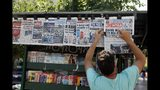 A vendor adjusts the front pages of the Greek newspapers as all of them refer to the election result in Athens, Monday, July 8, 2019. Conservative party leader Kyriakos Mitsotakis' New Democracy party won 39.8% of the Sunday vote, giving him 158 seats in the 300-member parliament, a comfortable governing majority. (AP Photo/Thanassis Stavrakis)