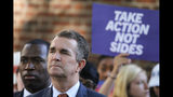 Virginia Gov. Ralph Northam, right, listens to speakers along with Richmond Mayor Levar Stoney, left, during a rally at the State Capitol in Richmond, Va., Tuesday, July 9, 2019. Governor Northam called a special session of the General Assembly to consider gun legislation in light of the Virginia Beach Shootings. (AP Photo/Steve Helber)