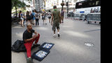 """A man sells tee shirts that he said he had made on Broadway in lower Manhattan, also known as the """"Canyon of Champions,"""" one day ahead of a ticker-tape parade and City Hall ceremony for the four-time World Cup winning U.S. women's soccer team, Tuesday, July 9, 2019, in New York. (AP Photo/Kathy Willens)"""