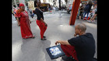"""A man sells tee shirts that he said he had made along Broadway in Lower Manhattan, also known as the """"Canyon of Champions,"""" one day ahead of a ticker-tape parade and City Hall ceremony for the four-time World Cup winning U.S. women's soccer team, Tuesday, July 9, 2019, in New York. (AP Photo/Kathy Willens)"""