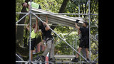 Workers assemble a press platform at City Hall one day ahead of a ticker-tape parade and ceremony honoring the four-time World Cup winning U.S. women's soccer team, Tuesday, July 9, 2019, in New York. (AP Photo/Kathy Willens)