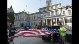 Workers unfurl a flag as they prepare New York City Hall one day ahead of Wednesday's ticker-tape parade and ceremony for the U.S. Women's four-time World Cup winning soccer team, Tuesday, July 9, 2019, in New York. (AP Photo/Kathy Willens)