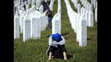 A woman rests at the memorial cemetery, prior to the funeral in Potocari, near Srebrenica, Bosnia, Thursday, July 11, 2019. The remains of 33 victims of the Srebrenica massacre will be buried 24 years after Serb troops overran the eastern Bosnian Muslim enclave of Srebrenica and executed some 8,000 Muslim men and boys, which international courts have labeled as an act of genocide. (AP Photo/Darko Bandic)