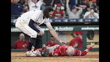 Houston Astros' Jake Marisnick, left, checks on Los Angeles Angels catcher Jonathan Lucroy after they collided at home plate during the eighth inning of a baseball game Sunday, July 7, 2019, in Houston. Marisnick was called out under the home plate collision rule. Lucroy was carted off the field. (AP Photo/David J. Phillip)