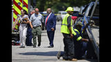 Investigators walk to the crime scene, Tuesday, July 9, 2019, in Cleveland. Police investigating the shooting death of a man in a vacant lot say they also found the bodies of a woman and two children in a nearby house. Authorities aren't saying how the three found inside the house Tuesday died, but they did say the four deaths are connected. (AP Photo/David Dermer)