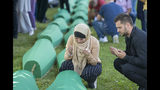 Mourners pray next to coffins in Potocari near Srebrenica, Bosnia, Thursday, July 11, 2019. The remains of 33 victims of the Srebrenica massacre will be buried 24 years after Serb troops overran the eastern Bosnian Muslim enclave of Srebrenica and executed some 8,000 Muslim men and boys, which international courts have labeled as an act of genocide. (AP Photo/Darko Bandic)