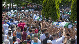 Coffins are being carried for the funeral in Potocari near Srebrenica, Bosnia, Thursday, July 11, 2019. Thousands of mourners, including relatives of the victims, are gathering for a commemoration on the 24th anniversary of the Srebrenica massacre, the worst mass killing in Europe since World War II. The ceremony at a memorial site near Srebrenica included the burial of 33 newly identified victims of the July 11-22, 1995 massacre in which more than 8,000 Bosnian Muslim men and boys were killed in and around the U.N.-protected enclave by Bosnian Serb troops during the Bosnian civil war. (AP Photo/Darko Bandic)