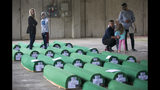 Relatives inspect coffins prepared for burial, in Potocari near Srebrenica, Bosnia, Wednesday, July 10, 2019. The remains of 33 victims of Srebrenica massacre will be buried on July 11, 2019, 24 years after Serb troops overran the eastern Bosnian Muslim enclave of Srebrenica and executed some 8,000 Muslim men and boys, which international courts have labeled as an act of genocide. (AP Photo/Darko Bandic)