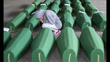A girl inspects coffins prepared for burial, in Potocari near Srebrenica, Bosnia, Wednesday, July 10, 2019. The remains of 33 victims of Srebrenica massacre will be buried on July 11, 2019, 24 years after Serb troops overran the eastern Bosnian Muslim enclave of Srebrenica and executed some 8,000 Muslim men and boys, which international courts have labeled as an act of genocide. (AP Photo/Darko Bandic)