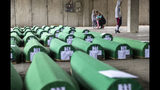Relatives inspect coffins prepared for burial in Potocari near Srebrenica, Bosnia, Wednesday, July 10, 2019. The remains of 33 victims of Srebrenica massacre will be buried on July 11, 2019, 24 years after Serb troops overran the eastern Bosnian Muslim enclave of Srebrenica and executed some 8,000 Muslim men and boys, which international courts have labeled as an act of genocide. (AP Photo/Darko Bandic)
