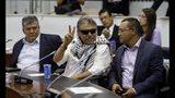 El ex rebelde de las FARC, el legislador Jesús Santrich, hace la señal de la victoria a periodistas cuando asiste a una sesión de la cámara baja en Bogotá, el miércoles 12 de junio de 2019. (AP Foto/Fernando Vergara)