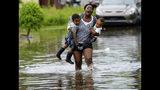 Terrian Jones reacciona cuando siente que algo se mueve en el agua alrededor de sus pies mientras carga a Drew y Chance Furlough en la calle Belfast en Nueva Orleans durante inundaciones causadas por una tormenta en el Golfo de México el miércoles 10 de julio de 2019. (AP Foto/Matthew Hinton)