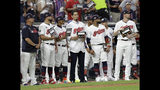 "FILE - In this July 9, 2019, file photo, Cleveland Indians pitcher Carlos Carrasco, center without a hat, stands with Indians teammates during the fifth inning of the baseball All-Star Game in Cleveland, as part of Major League Baseball's ""Stand Up to Cancer"" campaign. Carrasco, who was diagnosed with leukemia and was honored during Tuesday's, July 9 All-Star Game, will throw a bullpen session and he's confident he can overcome his condition and pitch again for Cleveland this season. (AP Photo/Tony Dejak, File)"