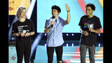 "FILE - In this April 25, 2019, file photo, Cameron Boyce, center, speaks at WE Day California, as Macy Lillard, left, and Jazzy Satten look on at The Forum in Inglewood, Calif. Actor Cameron Boyce, known for his roles in the Disney Channel franchise ""Descendants"" and the Adam Sandler ""Grown Ups"" movies, died Saturday, July 6, 2019, at his home in Los Angeles, according to his spokesperson. He was 20. (Photo by Chris Pizzello/Invision/AP, File)"