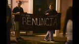 """Citizens carrying a banner that reads in Spanish """"Ricarod Rosello, renounce"""" protest near the executive mansion denouncing a wave of arrests for corruption that has shaken the country and demanding the resignation of Gov. Ricardo Rosello, in San Juan, Puerto Rico, Thursday, July 11, 2019. Puerto Rico's former secretary of education and 5 other people have been arrested on charges of steering federal money to unqualified, politically connected contractors. U.S. Attorney for Puerto Rico Rosa Emilia Rodríguez said Gov. Rossello was not involved in the investigation. (AP Photo/Carlos Giusti)"""