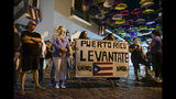 """Dozens of citizens holding a sign that reads in Spanish """"Puerto Rico rise up, unite now!"""" protest near the executive mansion denouncing a wave of arrests for corruption that has shaken the country and demanding the resignation of Gov. Ricardo Rosello, in San Juan, Puerto Rico, Thursday, July 11, 2019. Puerto Rico's former secretary of education and 5 other people have been arrested on charges of steering federal money to unqualified, politically connected contractors. U.S. Attorney for Puerto Rico Rosa Emilia Rodríguez said Gov. Rossello was not involved in the investigation. (AP Photo/Carlos Giusti)"""
