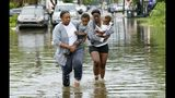 Jalana Furlough carries her son Drew Furlough as Terrian Jones carries Chance Furlough in New Orleans after flooding Wednesday, July 10, 2019. (AP Photo/Matthew Hinton)