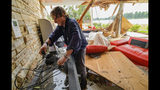 Eric Ehlenberger, a physician and neon artist, goes through his damaged home in New Orleans on Wednesday, July 10, 2019, following a storm that swamped the city and paralyzed traffic. Ehlenberger said his wife was able to crawl out safely. (AP Photo/Matthew Hinton)