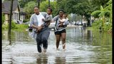 Jalana Furlough carries her son Drew Furlough as Terrian Jones carries Chance Furlough on Belfast Street near Eagle Street in New Orleans after flooding from a tropical wave system in the Gulf Mexico that dumped lots of rain in Wednesday, July 10, 2019. (AP Photo/Matthew Hinton)