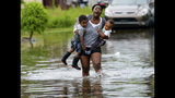 Terrian Jones reacts as she feels something moving in the water at her feet as she carries Drew and Chance Furlough to their mother on Belfast Street in New Orleans during flooding from a storm in the Gulf Mexico that dumped lots of rain Wednesday, July 10, 2019. (AP Photo/Matthew Hinton)