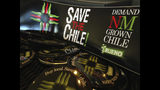 FILE - In this July 31, 2013 file photo, a collection of bumper stickers and buttons promoting New Mexico-grown chile sits on the order counter at Hello Deli restaurant in Albuquerque, N.M. The long-simmering battle between New Mexico and Colorado over which state grows the best chile is heating up. New Mexico Gov. Michelle Lujan Grisham went on the offensive Wednesday, July 10, 2019, after Colorado Gov. Jared Polis proclaimed on Twitter that hot peppers from Pueblo were the best and would be stocked in grocery stores in a four-state region. (AP Photo/Susan Montoya Bryan, File)