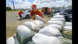 Trabajadores reclusos del departamento de policía de la municipalidad de St. Bernard trasladan costales de arena para los residentes en Chalmette, Luisiana, el jueves 11 de julio de 2019. (AP Foto/Matthew Hinton)