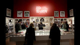 """In this Wednesday, July 10, 2019 photo, visitors look through merchandise for sale during a media preview of """"Ed Hardy: Deeper than Skin"""" at the de Young Museum in San Francisco. The exhibition opening Friday, July 12 sheds light on Hardy as a prolific artist and tattoo pioneer. (AP Photo/Jeff Chiu)"""