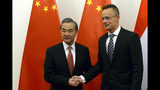 Chinese Foreign Minister Wang Yi, left, shakes hands with Hungarian Minister of Foreign Affairs and Trade Peter Szijjarto during their meeting in the latter's office in Budapest, Hungary, Friday, July 12, 2019. (Lajos Soos/MTI via AP)