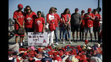 Fans stand next to a makeshift shrine in honor of Los Angeles Angels pitcher Tyler Skaggs outside Angel Stadium before the team's baseball game against the Seattle Mariners on Friday, July 12, 2019, in Anaheim, Calif. (AP Photo/Marcio Jose Sanchez)