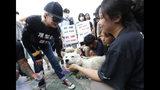 La actriz estadounidense Kim Basinger, izquierda, saluda a una mascota durante una protesta contra el consumo de carne de perro frente a la Asamblea Nacional en Seúl, Corea del Sur, el viernes 12 de julio de 2019. (AP Foto/Ahn Young-joon)