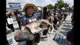 Miembros de Última Oportunidad para Animales sostiene perros muertos falsos durante una protesta contra el consumo de carne de perro frente a la Asamblea Nacional en Seúl, Corea del Sur, el viernes 12 de julio de 2019. (AP Foto/Ahn Young-joon)