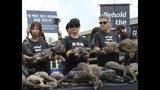La actriz estadounidense Kim Basinger, centro, sostiene un falso perro muerto durante una protesta contra el consumo de carne de perro frente a la Asamblea Nacional en Seúl, Corea del Sur, el viernes 12 de julio de 2019. (AP Foto/Ahn Young-joon)