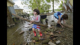 Delilah Campbell, 4, left, and her sister, Tallulah Campbell, 8, clear out driftwood and other debris in preparation of Tropical Storm Barry near New Orleans, La., Thursday, July 11, 2019. The area is normally a driveway at her family's home that is one of the few on land called batture on the outside of the Mississippi River levee at the border of Orleans and Jefferson Parishes. (AP Photo/Matthew Hinton)