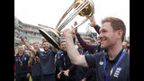 England's Eoin Morgan, right, and teammates celebrate with the trophy at the Oval in London, Monday, July 15, 2019 one day after they won the Cricket World Cup in a final match against New Zealand.(AP Photo/Frank Augstein)