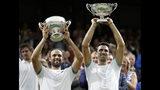 Los colombianos Juan Sebastián Cabal (izquierda) y Robert Farah levantan sus trofeos tras ganar la final de dobles de Wimbledon ante los franceses Nicolas Mahut y edouard Roger Vasselin, el sábado 13 de julio de 2019 (AP Foto/Kirsty Wigglesworth)