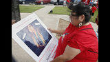 "FILE - In this Friday, June 14, 2019, file photo, Carmen Thompson, of El Reno, Okla., looks over a poster of her niece Emily Morgan who was murdered in 2016, before the start of a march to call for justice for missing and murdered indigenous women at the Cheyenne and Arapaho Tribes of Oklahoma in Concho, Okla. U.S. Senate staffers say officials missed a second deadline on July 8 to offer input on bills on Native American safety, and only one department has since provided ""partial comment."" (AP Photo/Sue Ogrocki, File)"